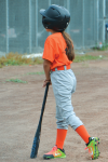 Girl in orange with baseball bat facing away