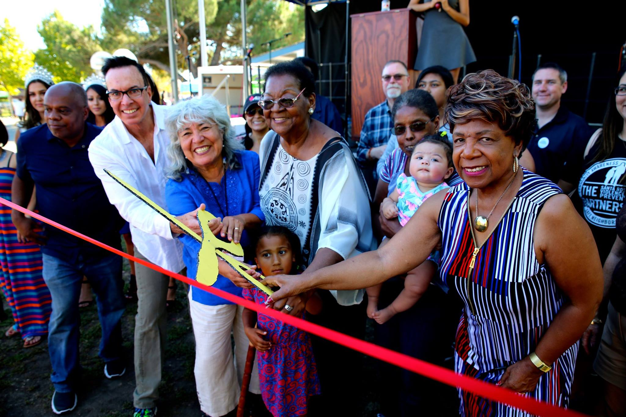 Group of diverse community members cutting ribbon at South Park Mural Ceremony