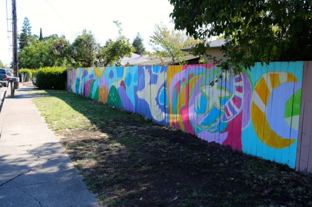 colorful fence mural along a neighborhood street