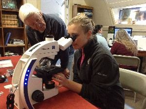 girl looking through microscope with teacher behind her helping