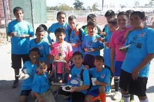 children in soccer uniforms posing for photo with team trophy