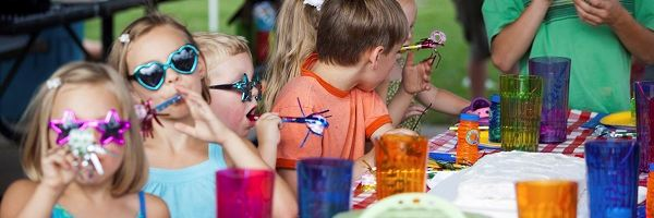 Kids at table with party glasses and party horns