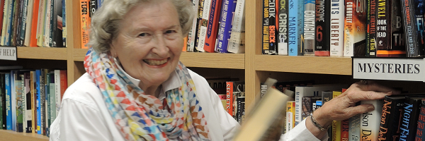 Volunteer senior smiling grabbing a book from library