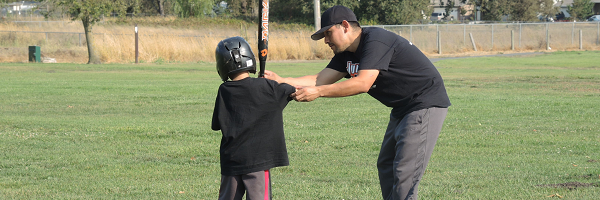 Junior Giants Volunteer teaching boy how to swing