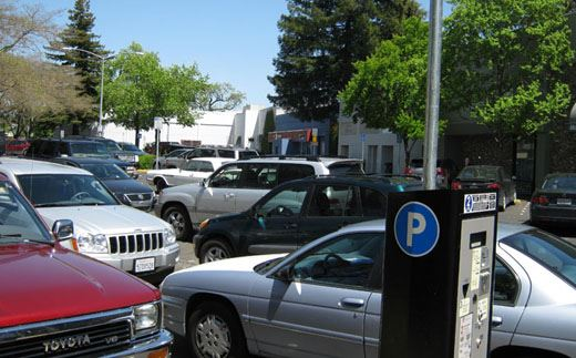 Image of cars in parking lot with pay station visible