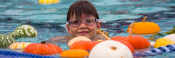 Boy swimming in middle of pumpkins
