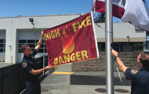 Red Flag being raised on flag pole at fire station
