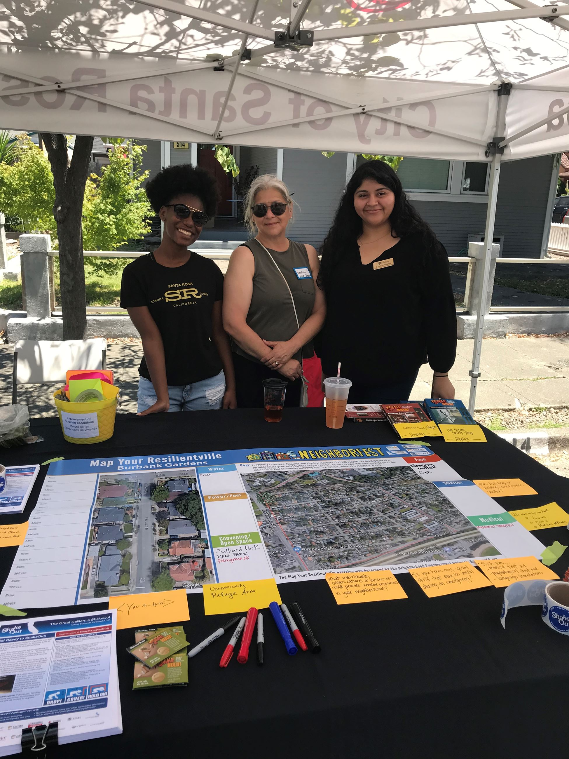 three women standing under a pop up tent next to a neighborhood map on a table