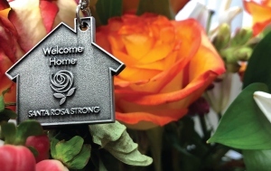 """Welcome home"" keychain with flowers in background"