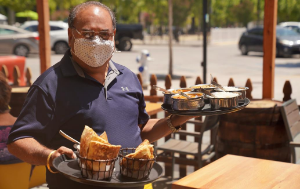 Man wearing mask, serving food outdoors