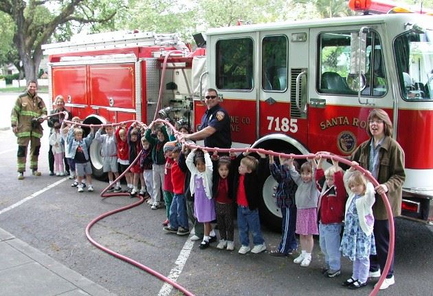 Children holding a fire hose beside a Santa Rosa Fire Department firetruck.