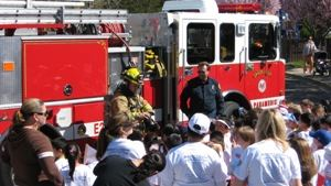 Fire fighters providing a safety demonstration to a crowd.