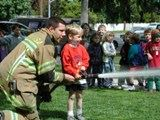 Firefighter helping a young boy operate a fire hose.