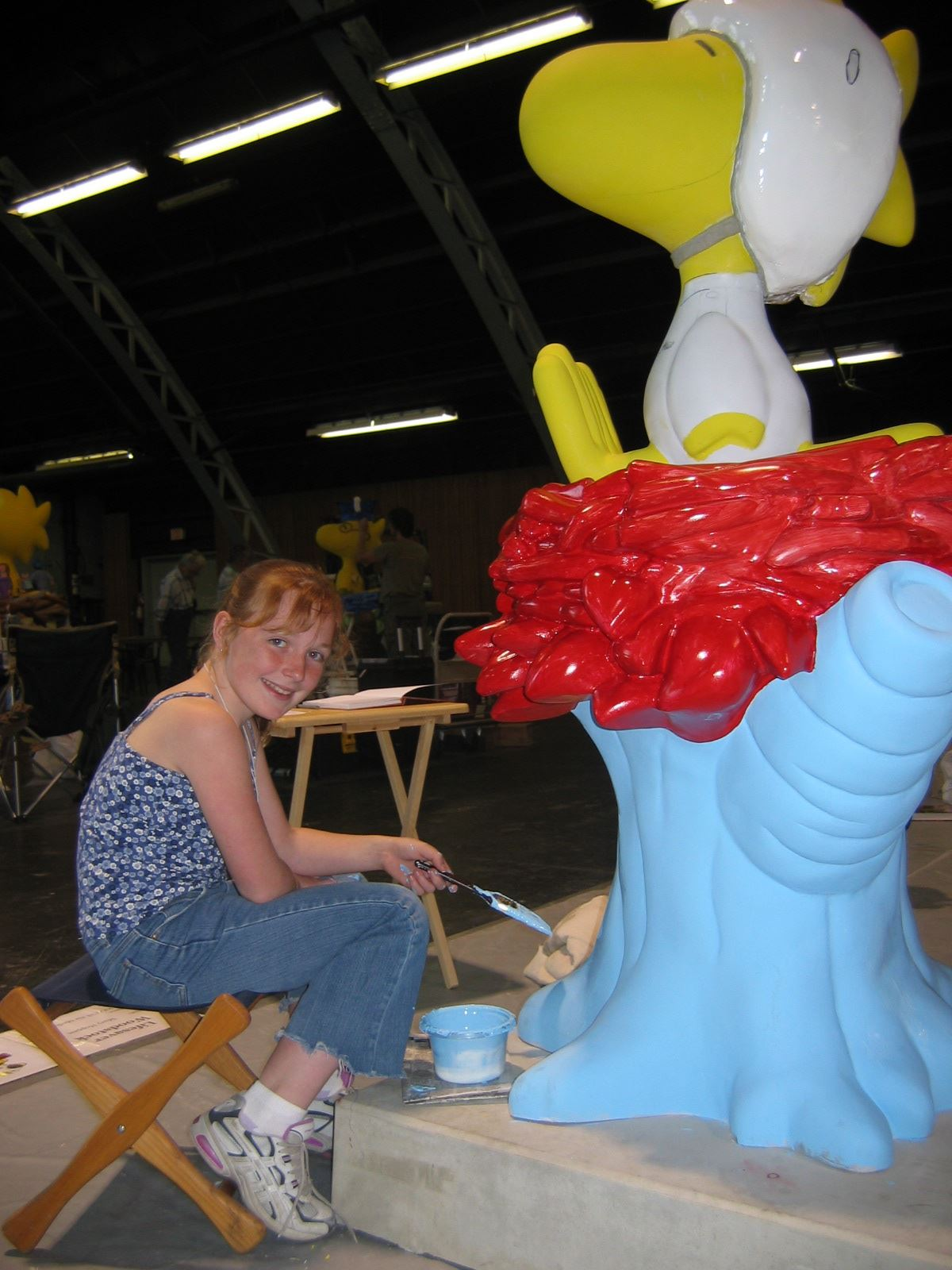 People painting a Woodstock statue