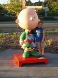 Young boy by a Charlie Brown statue