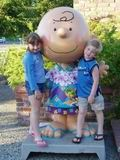 Two kids by a Charlie Brown statue