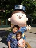 Young kids by a Charlie Brown statue
