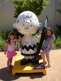 Young girls by a Charlie Brown statue